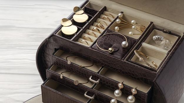 Взгляд сверху открытой коричневой кожаной шкатулки для драгоценностей. золотые украшения в коричневых кожаных аксессуарах органайзер