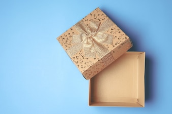 Top view of open gift box on blue background. Free space for text