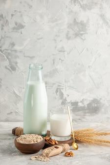 氷の背景に茶色の鍋にミルクスプーンとクルミのオーツ麦で満たされた開いたガラス瓶カップの上面図