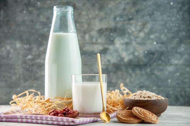 紫色の剥ぎ取られたタオルの上にスプーンクッキーオーツ麦のミルクと豆で満たされた開いたガラスカップボトルの上面図