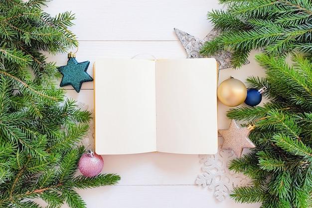 ぼろぼろの白い木製のテーブルの上の開いたノートブックとモミの枝、装飾、星、ボールの上面図。モックアップ