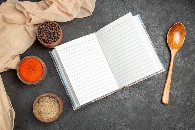 開いたノートブックタオルスプーンとさまざまなスパイスの上面図