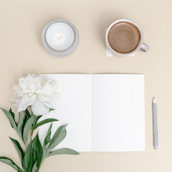 Вид сверху открытой записной книжки с чашкой кофе с цветком белого пиона креативное рабочее пространство в минималистском стиле