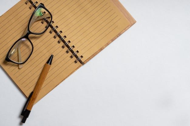 ペンまたは鉛筆と白い背景で隔離のメガネと開いているノートブックの上面図。フラットレイ、コピースペース。ビジネスコンセプト
