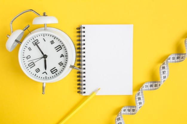 Вид сверху на открытый блокнот, белый будильник и белый сантиметр на желтом, плоской планировке