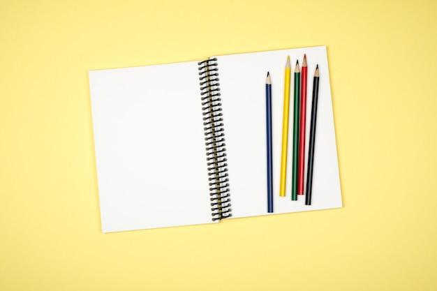 カラフルな机の上の開いているスパイラル空白ノートブックのトップビュー