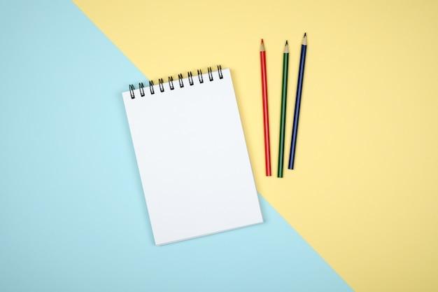 カラフルな机の上の開いているスパイラル空白のノートブックのトップビュー