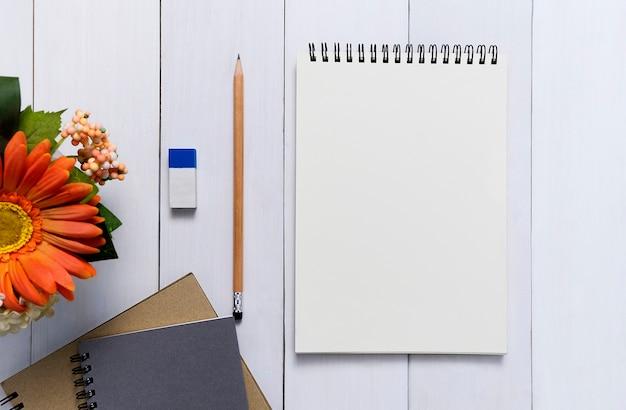 Вид сверху открытой спиральной пустой блокнот с карандашом на фоне дерева стола