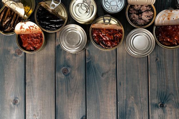 Вид сверху открытых банок с рыбными консервами на деревянной поверхности