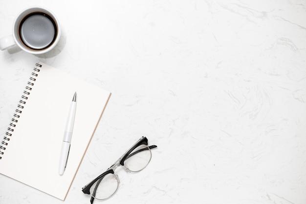 Вид сверху открытой тетради для заметок, ручки, очков и чашки кофе на белом мраморном фоне.
