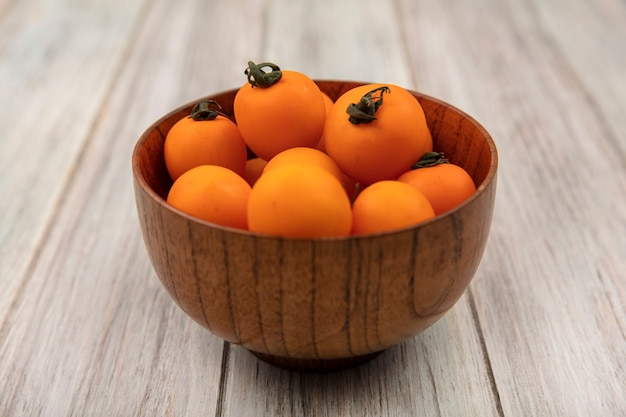 灰色の木製の背景の上の木製のボウルにオレンジ色のチェリートマトの上面図