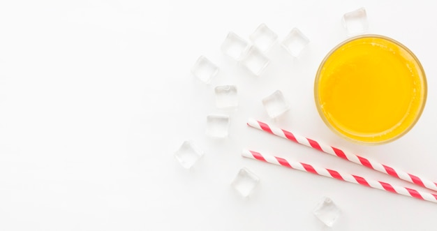 Вид сверху на стакан апельсинового сока с соломкой и копией пространства