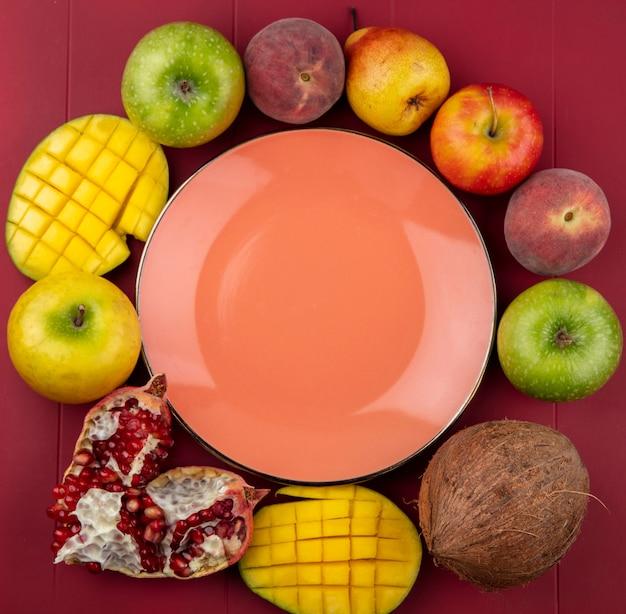 빨간 bakcground에 사과 코코넛 석류 복숭아 배 같은 신선한 과일과 오렌지 접시의 상위 뷰