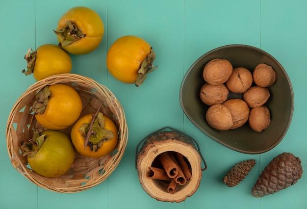 青い木製のテーブルに分離された柿の果実とボウルにクルミと木製の瓶にシナモンスティックとバケツのオレンジ色の丸みを帯びた柿の果実の上面図