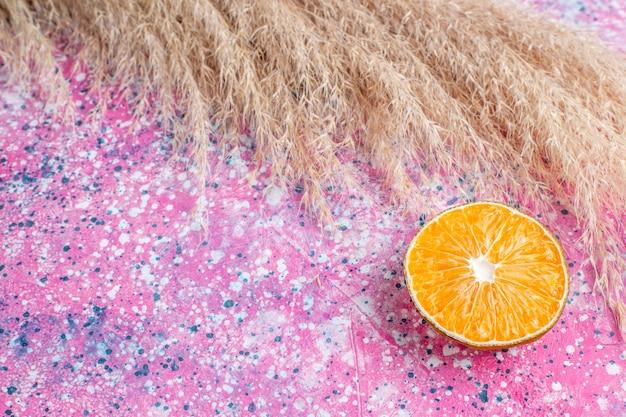 Вид сверху дольки апельсина на розовой поверхности