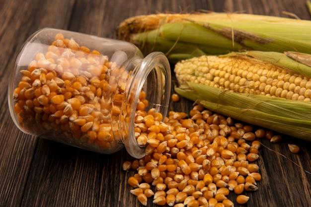Вид сверху органических и свежих мозолей с волосами с зернами кукурузы, выпадающими из стеклянной банки на деревянном столе