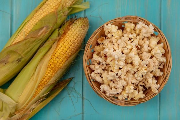 青い木製のテーブルの上のバケツにポップコーンと髪の有機と健康なトウモロコシの上面図