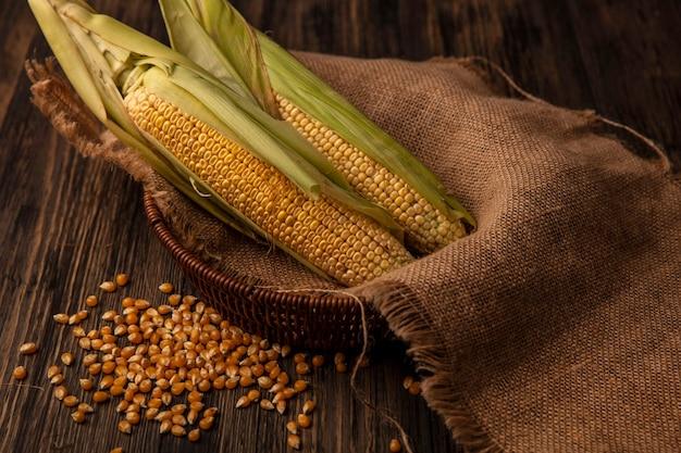 木製のテーブルで隔離の穀粒と袋布バケツに髪の毛を持つ有機新鮮なトウモロコシの上面図