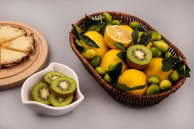 灰色の背景のボウルにキウイスライスとバケツにキウイキンカンやレモンなどの有機フルーツの上面図