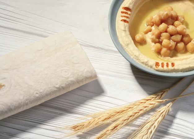 白い木製のテーブルの上のパンと小麦の有機フムスボウルのトップビュー