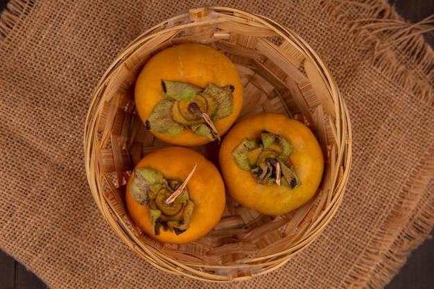 나무 테이블에 자루 천에 양동이에 유기 감 과일의 상위 뷰