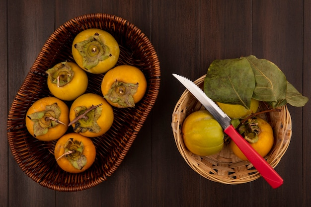 나무 테이블에 칼으로 양동이에 유기농 감 과일의 상위 뷰