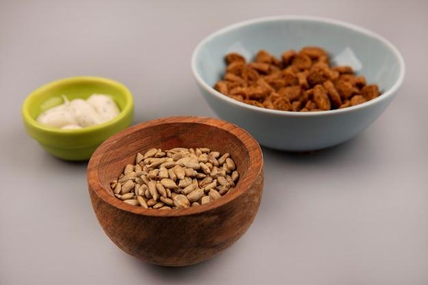 소스와 함께 맛있는 호밀 러스크와 나무 그릇에 유기 껍질 해바라기 씨앗의 상위 뷰