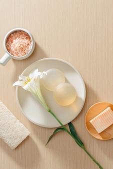 Вид сверху органических спа-продуктов по уходу за кожей с солью, цветами, натуральным мылом, полотенцами и пемзой
