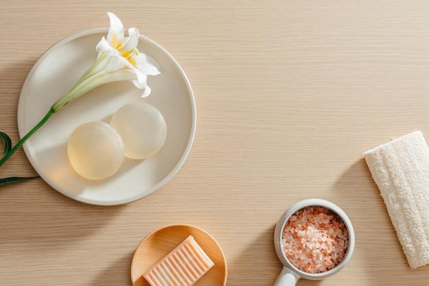 Вид сверху органических спа-продуктов по уходу за кожей с солью, цветами, полотенцами и рисовым мылом
