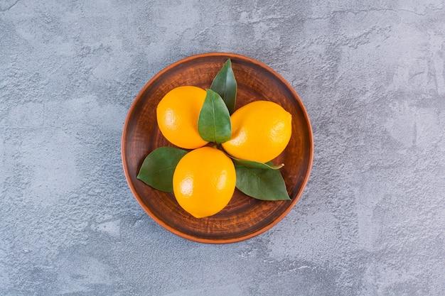 Вид сверху органических трех лимонов на деревянной тарелке над серым.