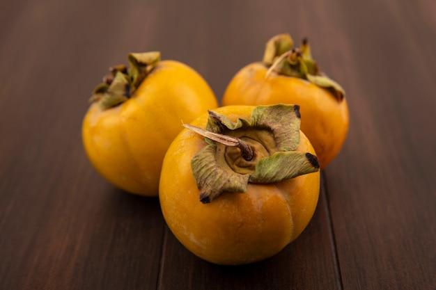 나무 테이블에 고립 된 유기 설 익은 감 과일의 상위 뷰