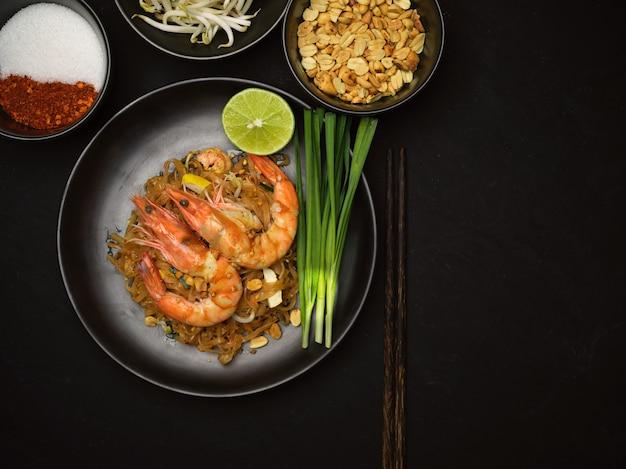 パッタイの上面図、ライムとチャイブの黒いセラミックプレートにエビの炒めたタイ麺