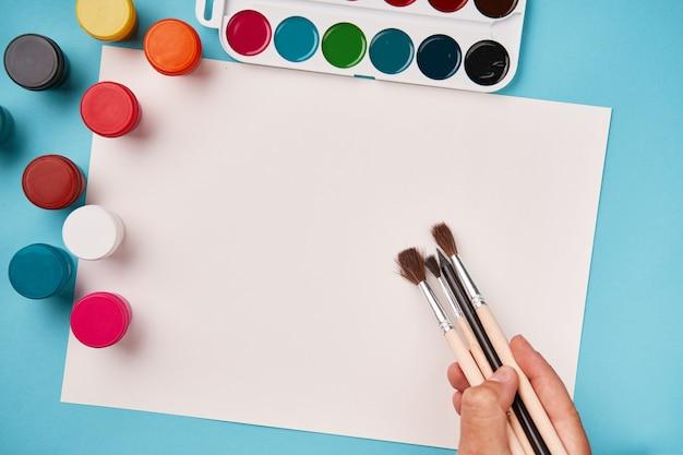 Вид сверху краски и кисти. холст макет. вид на школьный стол. класс искусств