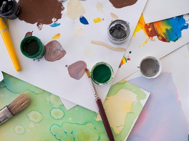 Вид сверху краски с кистями и бумагой