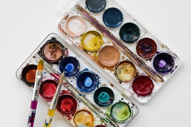 Вид сверху палитры кистей и акварельных красок