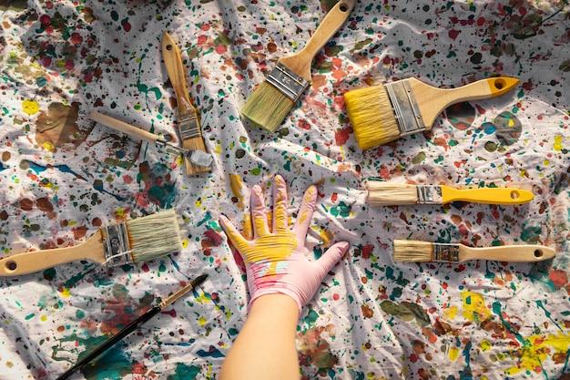Вид сверху кистей с краской и рукой художника