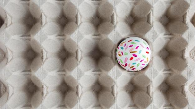 Вид сверху расписного пасхального яйца в картонной коробке