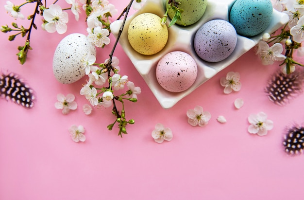 Вид сверху расписных пасхальных яиц и лотка для яиц на розовой поверхности