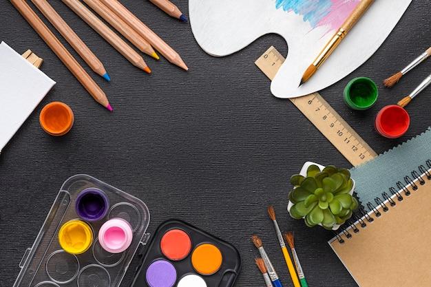 Вид сверху на набор для рисования с блокнотом и палитрой