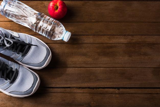 Вид сверху пары спортивной обуви, воды в бутылках и красного яблока на деревянном столе