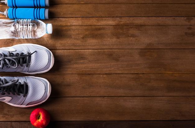 Вид сверху пары спортивной обуви, воды в бутылках, яблока и скакалки на деревянном столе, серых кроссовок и аксессуаров оборудования в фитнес-зале