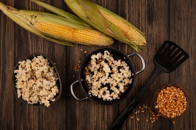 Вид сверху на сковороду с вкусным попкорном с зернами кукурузы со свежими кукурузными зернами, изолированными на деревянной миске на деревянном столе