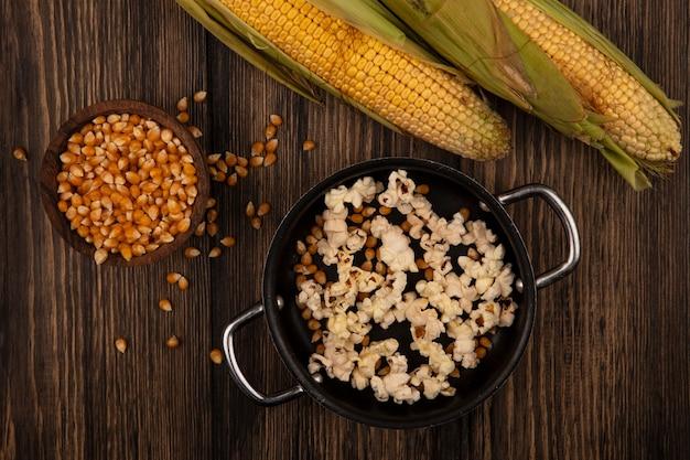 Вид сверху на сковороду с вкусным попкорном с кукурузными зернами и свежими кукурузными зернами, изолированную на деревянной миске на деревянном столе