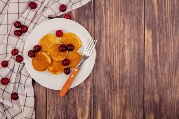 格子縞の布のチェリーとプレートのフォークとコピースペースを持つ木製の背景のパンケーキのトップビュー
