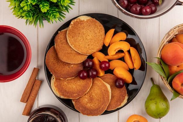 Вид сверху блинов с вишней и нарезанным абрикосом в тарелке и чашке кофе с грушей и абрикосами с корицей на деревянном фоне