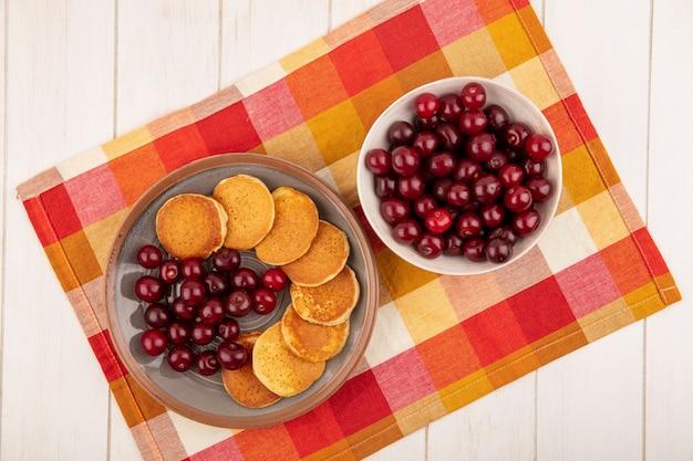 格子縞の布と木製の背景にプレートとチェリーのボウルのチェリーとパンケーキのトップビュー