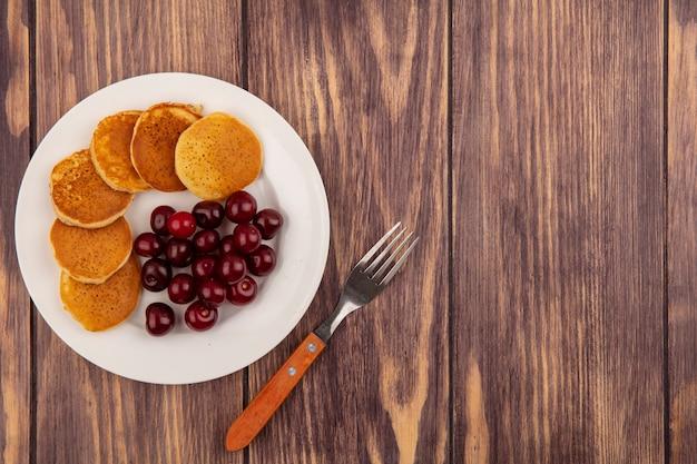 Вид сверху блины с вишней в тарелке и вилке на деревянном фоне с копией пространства