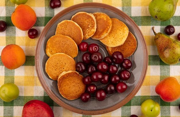 Вид сверху блины с вишней в тарелке и узор из абрикоса, персика, сливы, груши, вишни на фоне клетчатой ткани