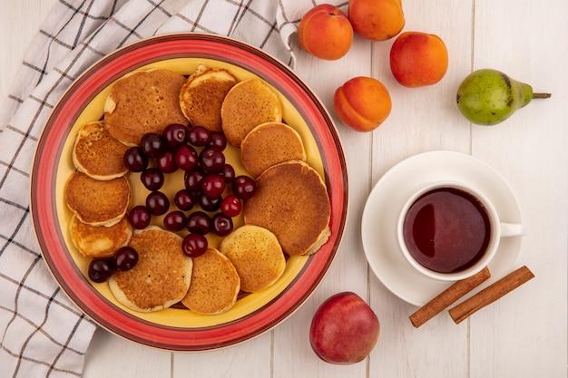 Вид сверху блины с вишней в тарелке на клетчатой ткани и абрикосами, персиковыми грушами с чашкой чая и корицей на деревянном фоне