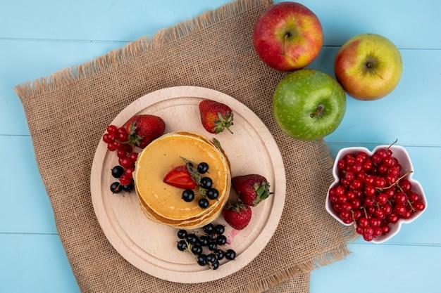 Вид сверху блинов с красной и черной смородиной и клубникой с цветными яблоками на синей поверхности